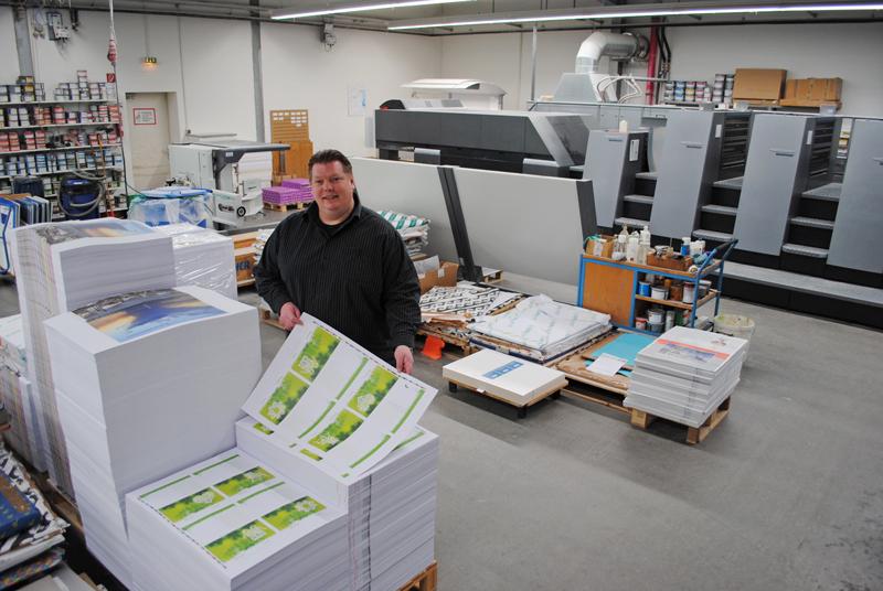 Geschäftsführer Axel Wüst im Drucksaal des Unternehmens. Im Hintergrund ist die große Druckmaschine zu sehen. Foto: Andrea Grotheer